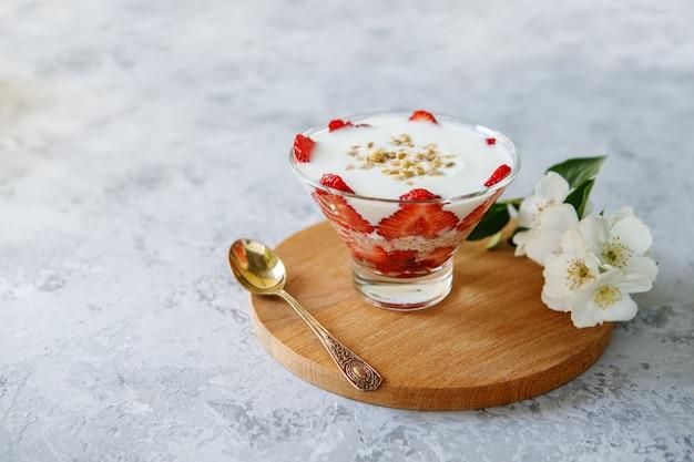 Café da manhã saudável de parfait de morango com frutas frescas e iogurte em uma mesa cinza