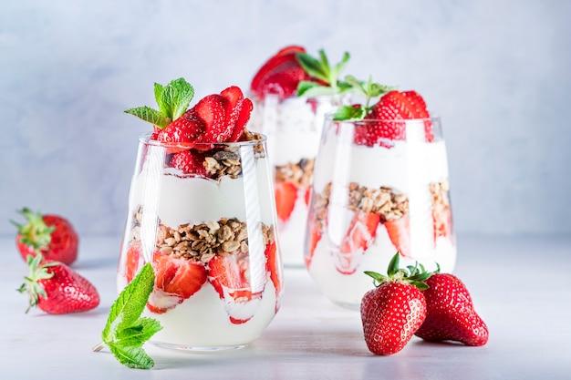 Café da manhã saudável de parfaits de morango feito com iogurte de morango fresco e muesli em copos