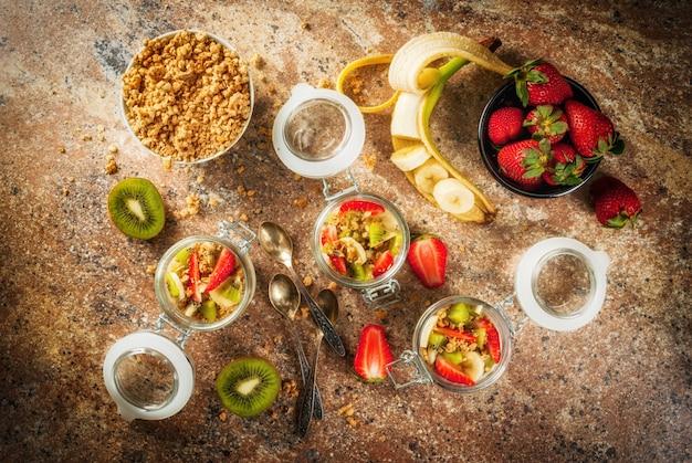 Café da manhã saudável dieta durante a noite aveia em um muesli de lata iogurte com granola caseira e frutas orgânicas - morango kiwi e banana na mesa de pedra com ingredientes e colheres
