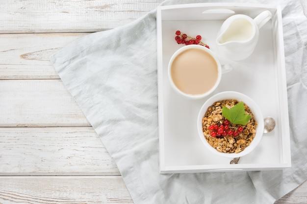 Café da manhã saudável do verão do granola, muesli com o jarro de leite com a decoração do corinto vermelho. vista do topo.