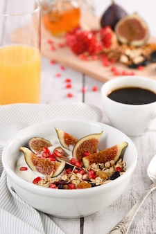 Café da manhã saudável e delicioso muesli de aveia com iogurte, figos, frutas secas e romã