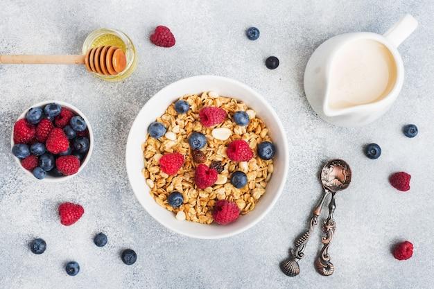 Café da manhã saudável. granola fresca, muesli com iogurte e frutas na mesa cinza. copie o espaço