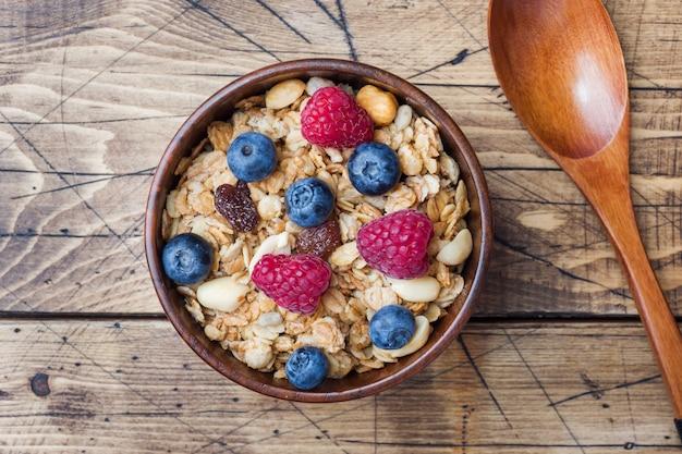 Café da manhã saudável. granola fresca, muesli com iogurte e frutas na superfície de madeira