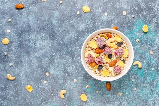 Café da manhã saudável. granola fresca, muesli com nozes e frutas congeladas. vista do topo. copie o espaço.