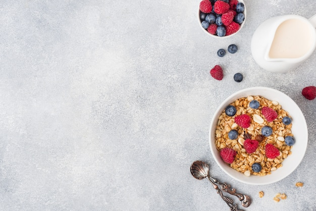 Café da manhã saudável. granola fresco, muesli com iogurte e bagas no fundo cinzento.