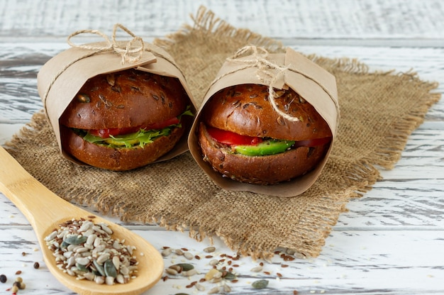Café da manhã saudável - hambúrguer com salmão defumado, folhas de salada e abacate, servido em um papel ofício em fundo de madeira, horizontal.