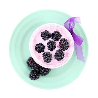 Café da manhã saudável - iogurte com amoras e muesli servido em frasco de vidro, isolado no branco