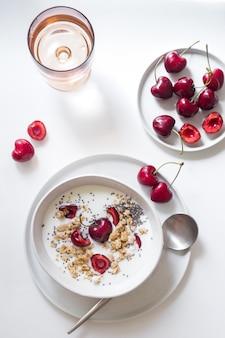 Café da manhã saudável. iogurte, sementes de chia, granola e cerejas em uma tigela branca