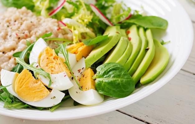 Café da manhã saudável. menu dietético. mingau de aveia e salada de abacate e ovos.