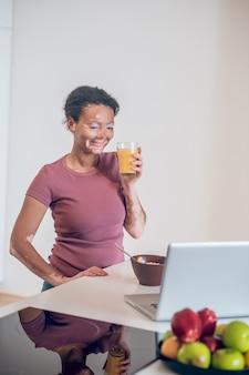 Café da manhã saudável. mulher jovem de pele escura tomando café da manhã em casa e bebendo suco de laranja