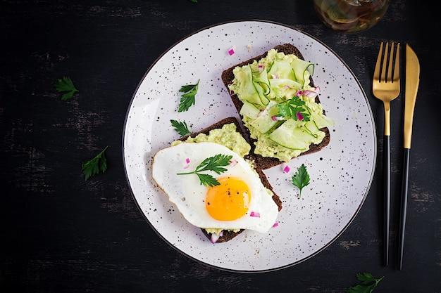 Café da manhã saudável. sanduíche com guacamole de abacate, pepino e ovo estrelado, no café da manhã ou lanche saudável. vista superior, sobrecarga, camada plana