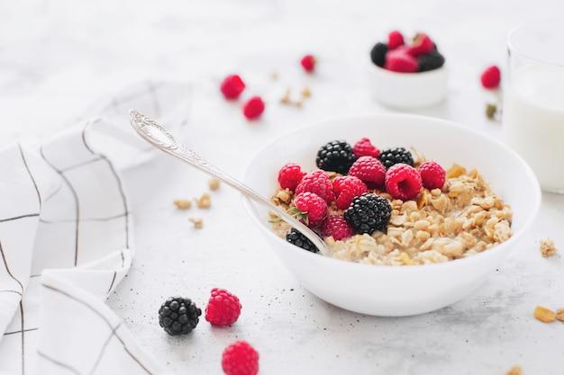 Café da manhã saudável, tigela branca cheia de granola, muesli, framboesa, amora preta na mesa de concreto cinza. alimentação saudável, eco, conceito de bio comida. refeição saborosa fresca em fundo cinza. foto de qualidade