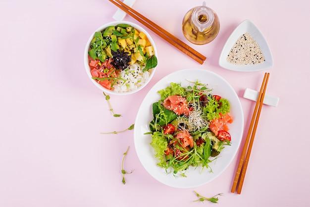 Café da manhã saudável. tigela de buda com arroz, manga, abacate e salmão e salada fresca com tomate, abacate, rúcula, sementes, salmão. conceito de comida saudável ... plano leigos