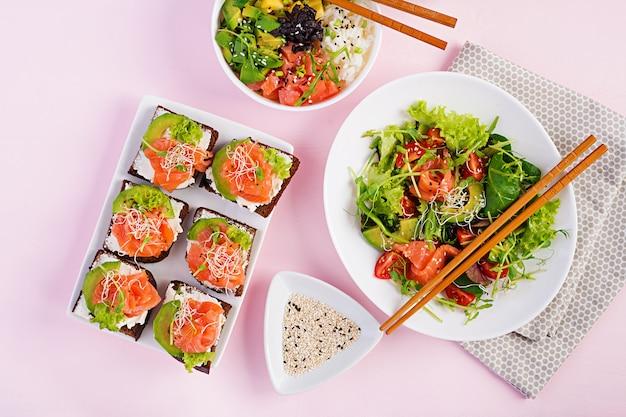 Café da manhã saudável. tigela de buda com arroz, manga, abacate e salmão e salada fresca com tomate, abacate, rúcula, sementes, sanduíche de salmão e salmão com abacate, queijo cremoso e microgreen. healt