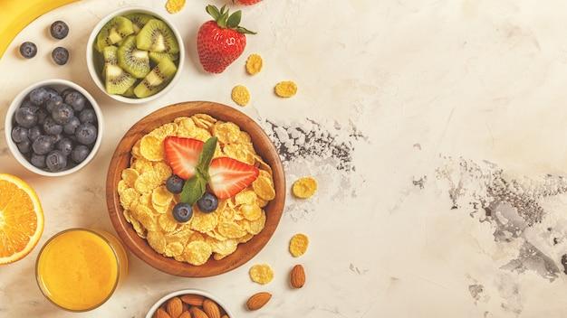 Café da manhã saudável - tigela de flocos de milho, bagas e frutas
