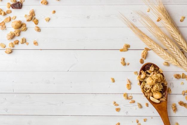 Café da manhã seco de flocos de aveia, grânulos e nozes. muesli em uma mesa de luz em uma colher de pau e orelhas