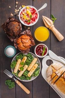 Café da manhã servido com bolinhos, salsichas grelhadas, suco, pão fresco e parfait em uma mesa de madeira escura.