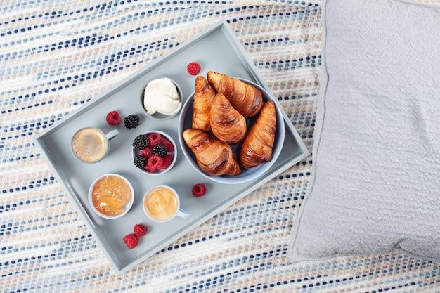 Café da manhã servido com café, croissants, frutas frescas, leite, creme, geléia