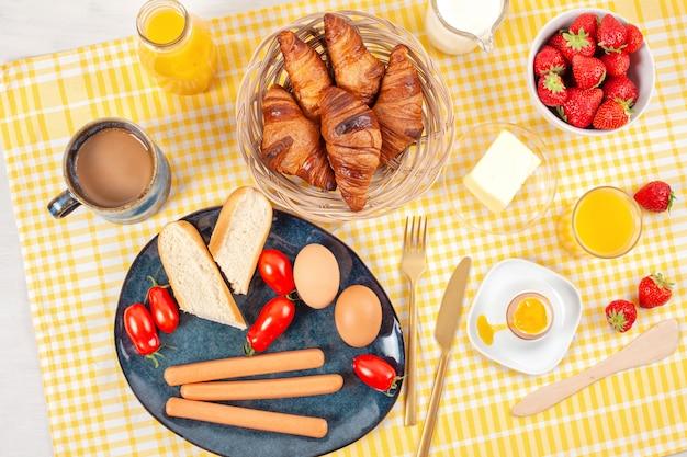 Café da manhã servido com café, croissants, salsichas, ovos, frutas frescas, leite, manteiga, suco de laranja