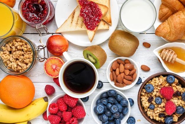 Café da manhã servido com café, suco de laranja, torradas, croissants, cereais, leite, nozes e frutas. dieta balanceada