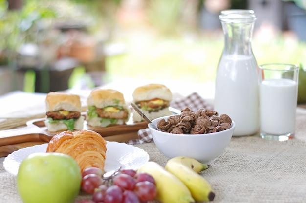 Café da manhã servido com sanduíche, leite, croissants, cereais e frutas