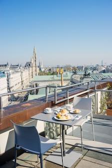 Café da manhã servido em um telhado do edifício da cidade europeia