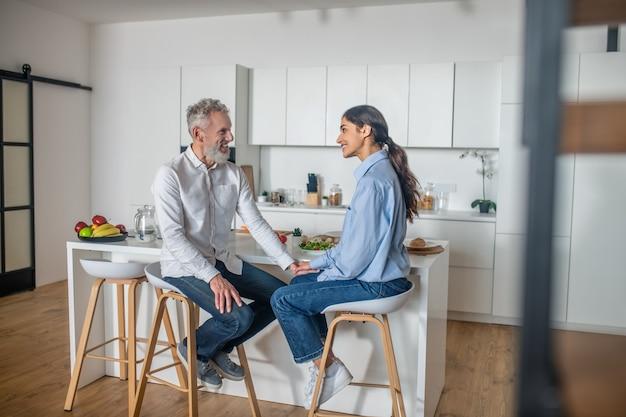 Café da manhã tão divertido. mulher jovem de cabelos escuros alimentando o marido e sorrindo