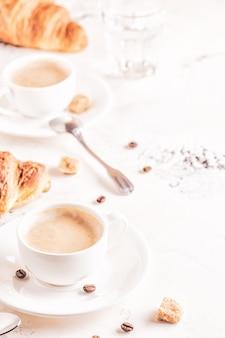 Café da manhã tradicional com croissants frescos na superfície branca, vertical.