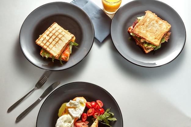 Café da manhã tradicional com ovos, sanduíches e suco de laranja na mesa