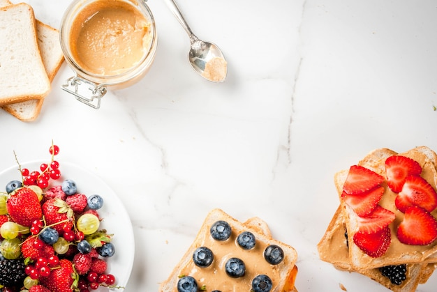 Café da manhã tradicional de verão americano e europeu: sanduíches de torrada com manteiga de amendoim, amora, maçã, pêssego, mirtilo, mirtilo, morango, banana. mesa de mármore branco. vista superior copyspace