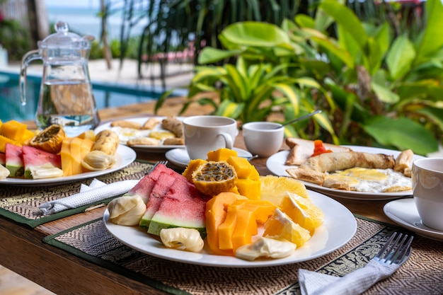 Café da manhã tropical de frutas, café e ovos mexidos e panqueca de banana para dois na praia, perto do mar