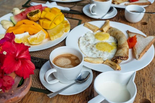 Café da manhã tropical de frutas, café e ovos mexidos e panqueca de banana