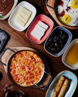 Café da manhã turco com menemen, ovos fritos, queijo, azeitonas, mel e manteiga.