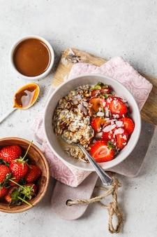 Café da manhã vegano. aveia com sementes de chia, bagas, sementes e caramelo em tigela branca.