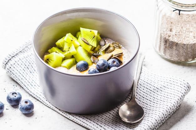 Café da manhã vegano. pudim de chia com kiwi, mirtilos e manteiga de amendoim.