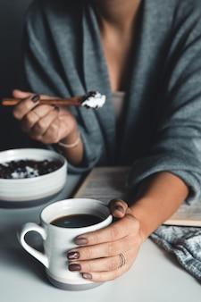 Café da manhã vegano saudável. mulher com suéter de lã comendo mingau de aveia com leite de amêndoa vegan com frutas, frutas e amêndoas.