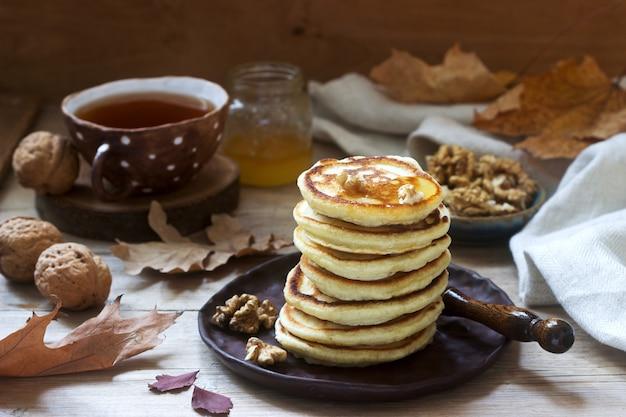 Café da manhã vegetariano de bolinhos fritos com mel, nozes e chá.