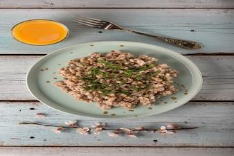 Café da manhã vegetariano. mingau de cevada cozido com ervas e um copo de suco de laranja em uma mesa de madeira clara.