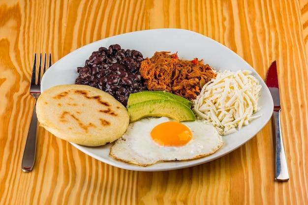 Café da manhã venezuelano de arepa, ovo frito, feijão preto, carne mechada, queijo branco e abacate