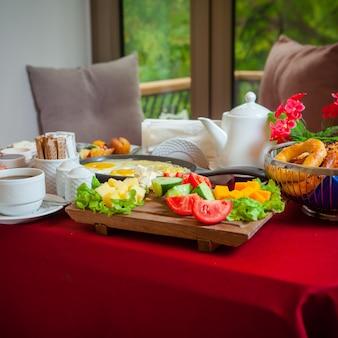 Café da manhã vista lateral em uma mesa com uma toalha de mesa vermelha ovos fritos, queijo queijo, pepino, tomate, alface, café
