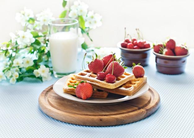 Café da manhã. waffles vienenses com morangos e cerejas em uma placa de madeira. primavera