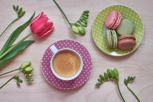 Café da primavera. macarons, café expresso em copo rosa, frésias e tulipas cor de rosa