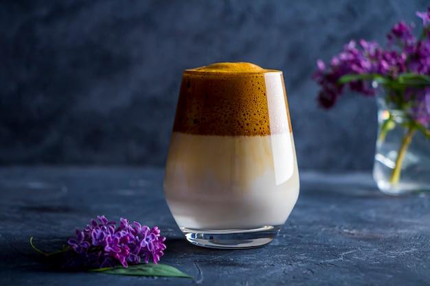 Café dalgona em copo alto e flores lilás