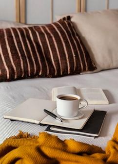 Café de alto ângulo e livros na cama