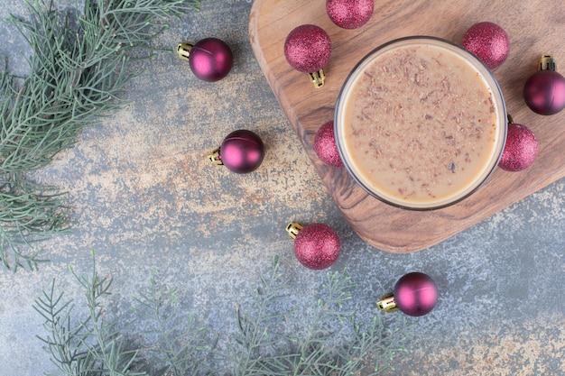 Café de aroma com bolas de natal na placa de madeira. foto de alta qualidade