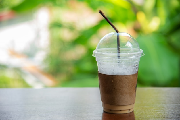 Café de cappuccino gelo em um copo no bokeh turva
