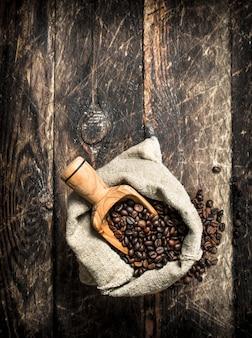 Café de grão em um saco. sobre um fundo de madeira.