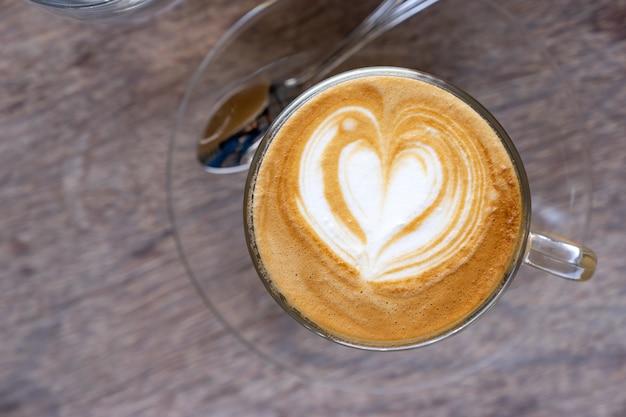Café de leite quente de vista superior com forma de coração de última arte em copo claro