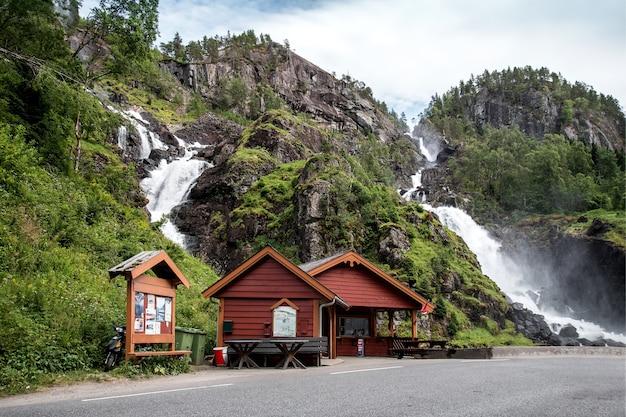 Café de madeira à beira da estrada com um poderoso riacho de cachoeira ao fundo