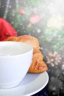 Café de natal. cappuccino quente de copo de vidro branco com croissants e decoração de natal